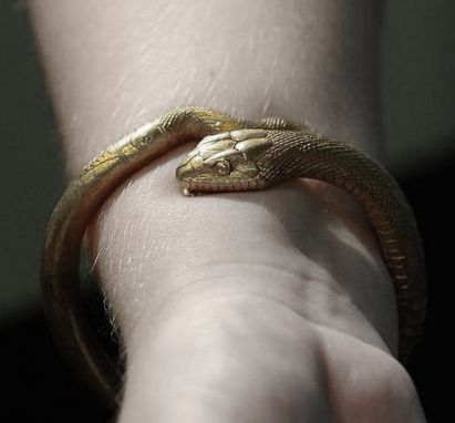 This is a traditional slave bracelet--it is usually made of cheap metal by the owner and given to the slave as a baby with technology installed to ensure that it would grow along with their wrist and that they couldn't remove it. The bracelets are mostly used as a constant reminder of their status.