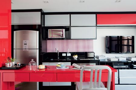 Em tons de cinza, preto e vermelho, os armários ocupam uma só parede, unindo cozinha e sala.   Foto Salvador Cordaro