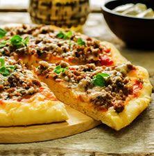 Αν το δεις να φτάνει στο τραπέζι μοιάζει με τεράστιο λαχματζούν, μόνο που αυτό έχει υπέροχη ζύμη πίτσας και φυσικά κρούστα από μπόλικη μοτσαρέλα