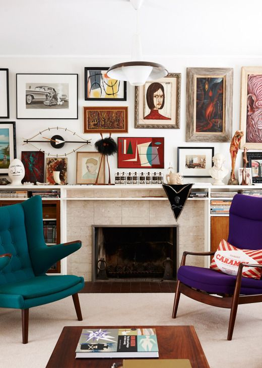 mismatched jewel tone modern chairs in front of a gallery wall