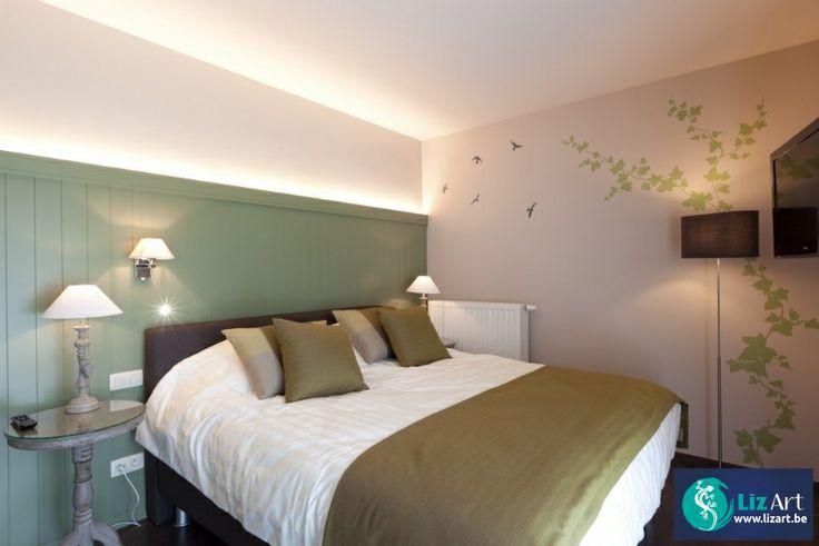 Decoratieve muurschildering van klimop in een hotelkamer