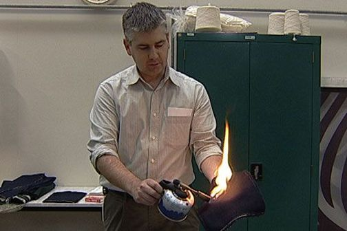 Dr Stewart Collie of AgResearch, Lincoln demonstrates the flame resistance of a new fabric.