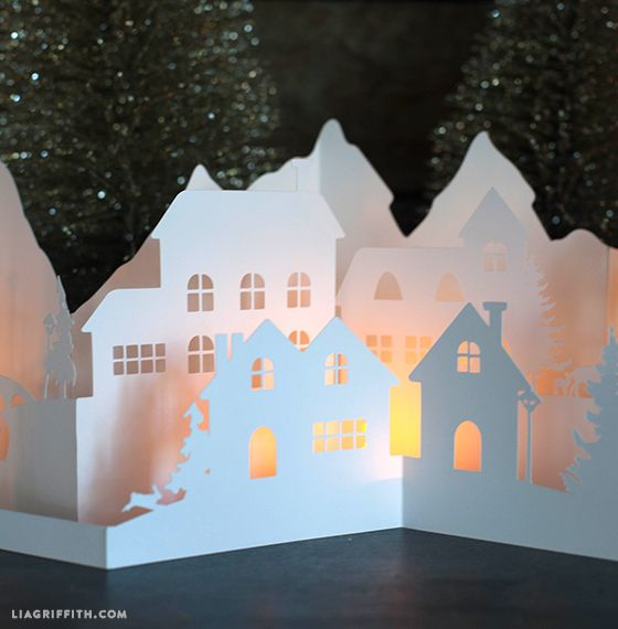 DIY - Paper cut Winter Village. This winter village has a mountain scape in the background with little village houses, clock towers, light poles and trees in the front two layers. The cut also features a bridge and deer, a rabbit and fox.