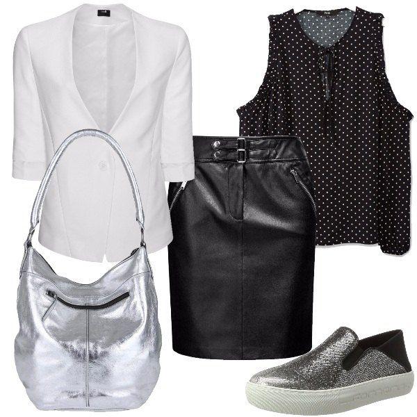 Total look formato da un blazer in bianco, una gonna in fintapelle nera, una maglietta nera a pois bianchi che lascia le spalle scoperte, una borsa in pelle silver e un paio di sneakers brillanti.