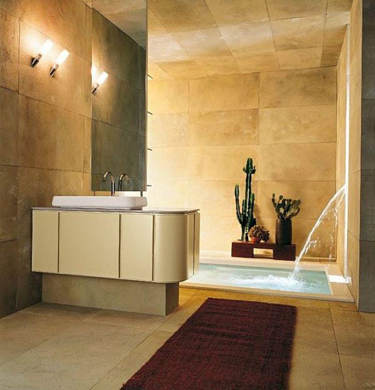 Bagno moderno grande interamente rivestito in lastre effetto pietra con vasca interrata e sorgente d'acqua sul muro