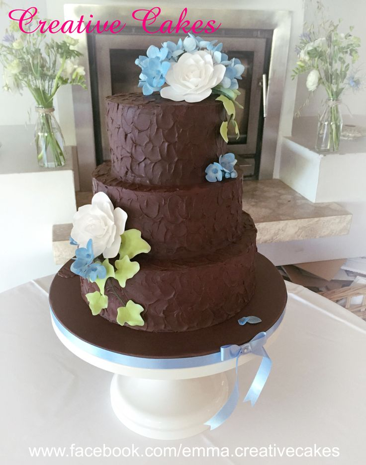 Rustic chocolate wedding cake made with chocolate ganache and decorated with Camilia's, ivy and blue hydrangea flowers - all designed and hand made by Creative Cakes