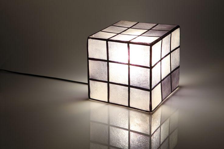 Χειροποίητο φωτιστικό από fiberglass, σε σχήμα κύβου. Μπορεί να χρησιμοποιηθεί ως φωτιστικό τραπεζιού ή οροφής.  Διαστάσεις: 20 x 20cm Xρώμα: μαύρο/άσπρο/γκρι  Ως κρεμαστό φωτιστικό, δίνει φως και άποψη στο χώρο. Ως επιτραπέζιο φωτιστικό, μπορεί να τοποθετηθεί σε όλους τους χώρους (ακόμα και σε εξωτερικό), σε ράφι ή στο πάτωμα, ενώ μπορεί να χρησιμοποιηθεί και σαν night light σε παιδικό δωμάτιο.