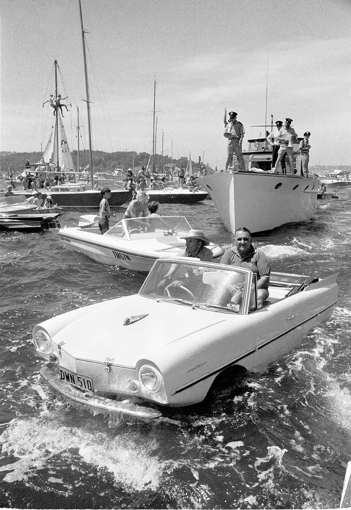 Amphicar on Harbour at start of Sydney to Hobart yacht race, c.1971/ by Australian Photographic Agency.