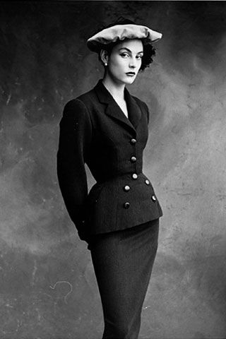 A draper par excellence, Balenciaga had a stable of models at his beck and call. His favorite was Colette, she of the broad shoulders and jutting, angular hips. When fitting his tailored suits with signature nipped waists and rounded hips on other girls, he used padding to achieve a fuller silhouette. The wishbone buttoning on this 1950 suit accentuates the model's hourglass shape.    Model wearing single-breasted skirt suit with wishbone buttoning by Balenciaga, Vogue, 1950.  Photo: Irving…