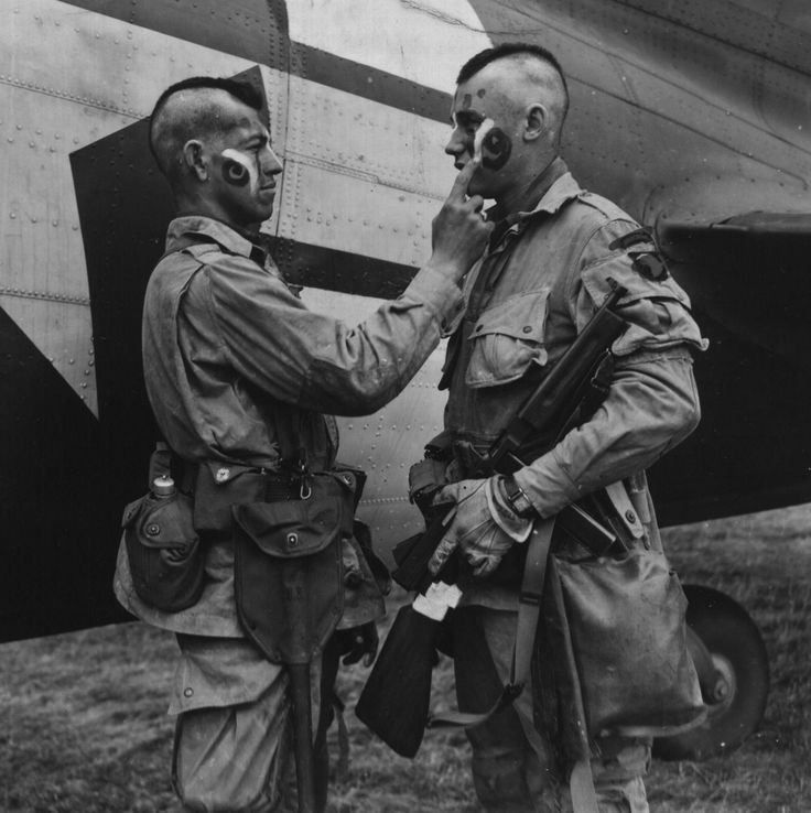 American paratroopers from the 101st Airborne applying paint to each other on the eve (June 5, 1944) of their jump into France in support of the Allied invasion of Normandy.