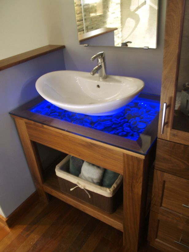 Every spa-inspired bathroom needs the proper mood lighting to create a soothing environment. Licensed contractor Matt Muenster enhanced his-and-her vanities in this modern bathroom by adding creative picture-frame tops. Underneath the glass tops he added various rocks and pebbles and then spread LED rope lighting around the edges. When lit, the countertops appear as glowing rock bed gardens in a vibrant shade of blue.