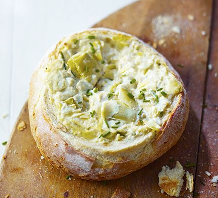 """Jim Proby's Baked Artichoke Bread"" INGREDIENTS 400g round cob loaf 2 x 390g tins artichoke hearts, drained 140g light mayonnaise 140g Parmesan (or vegetarian alternative), grated two pinches of garlic salt small bunch chives, finely chopped extra crusty bread chunks, crackers or crunchy tortillas, to serve METHOD  1. Heat oven to 180C. Slice the top off and hollow out the loaf. Break the artichoke hearts into chunks, place in a bowl with the mayonnaise, Parmesan, garlic salt and a good…"