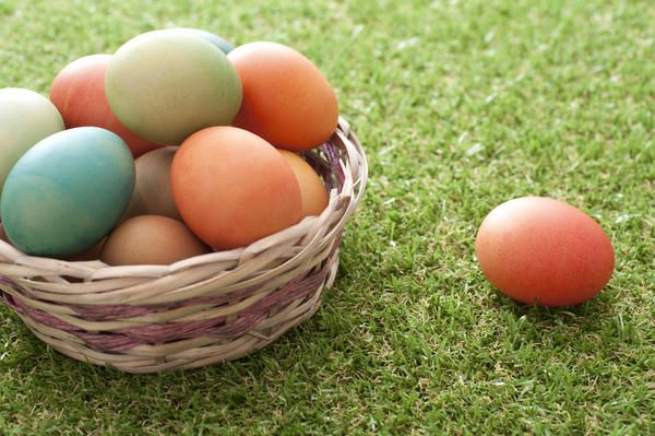 Love this image: Wicker basket of multicolored dyed Easter Eggs outdoors in spring sunshine on neatly trimmed green grass with a single egg alongside - By stockarch.com user: easterstockphotos