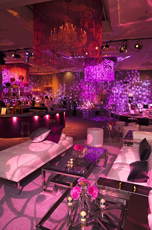 Guests can relax on white couches trimmed in silver and punctuated with purple velvet pillows.