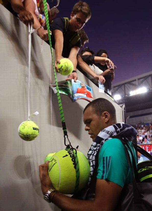 20 Jan 2016: Jo-Wilfried Tsonga of France signs autographs for fans following his second round win over Omar Jasika of Australia. (AP Photo/Aaron Favila)