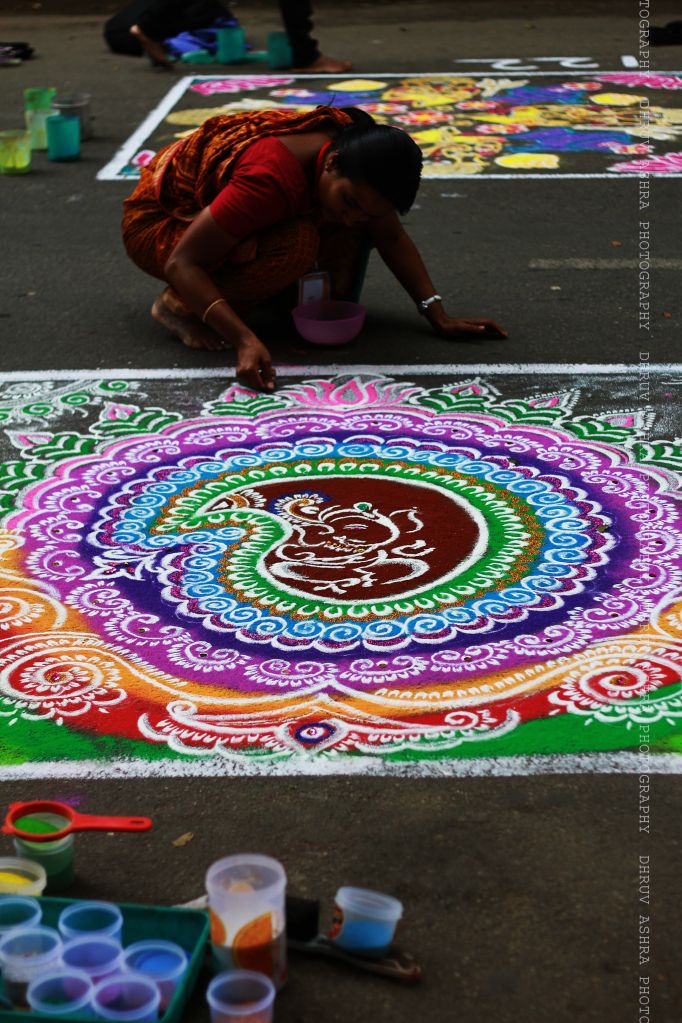 (in Rangoli) Kolam is a form of sand painting that is drawn using rice powder by female members of the family in front of their home. It is widely practiced by Hindus in South India. A kolam is a sort of painted prayer - a line drawing composed of curved loops, drawn around a grid pattern of dots. Kolams are thought to bestow prosperity to homes.