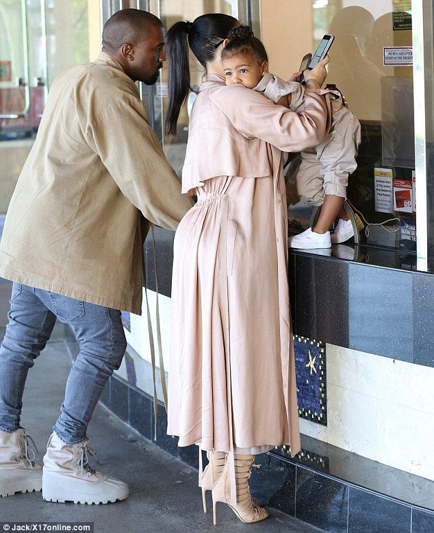 Three please: As Kanye picked up the tickets, Kim grappled with her daughter and two mobile phones: