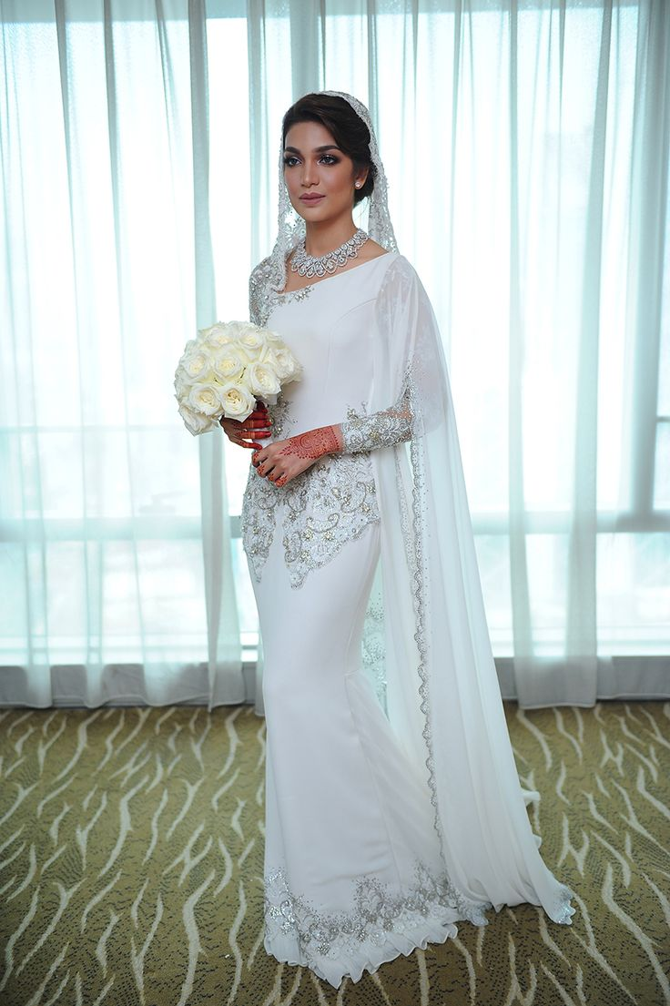 Simple petite white bridal bouquet with sparkling grey necklace and flowing cape // Malaysian TV personalities Amar Baharin and Amyra Rosli tied the knot in a lavish nikah (solemnisation ceremony) in Kuala Lumpur, Malaysia. The bride wore a jaw-dropping bespoke blush ball gown made of French lace and Swarovski crystals, while the groom looked every part the knight in shining armour in his Prince Charming-inspired suit by Rizman Ruzaini Creations. Here, we take you inside this celebrity…
