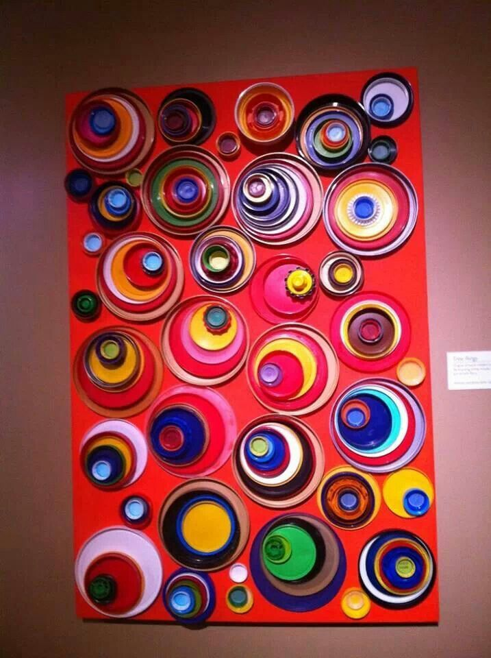 Paint lids of various shapes and sizes and glue to a canvas. Can be customized with any colors to fit any decor.