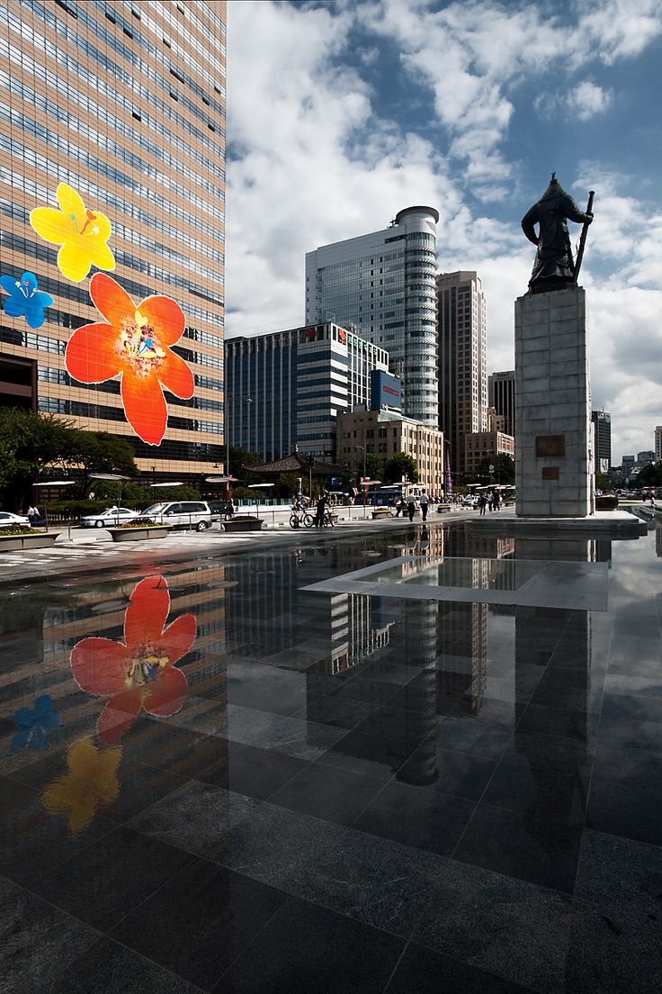 Downtown Seoul, very near Seoul city hall. Summer is full of activity at the base of the statue of Admiral Yi Sun Sin (이순신). Seoul, South Korea