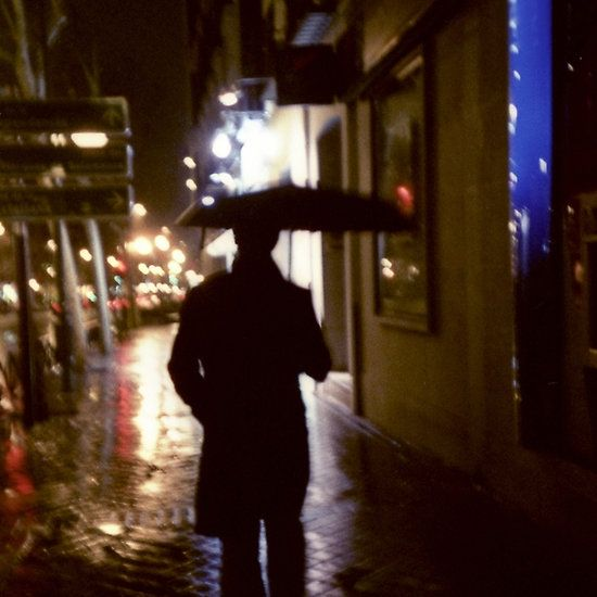 Man walking in street at night in rain color 35mm analogue photojournalism portrait photograph. #redbubble