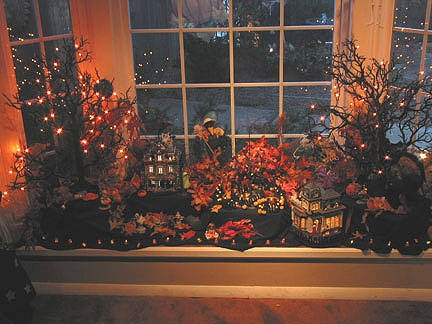 Great idea for the front window seat!  The lit up branches, leaves & fabric make a good backdrop for any fall display.