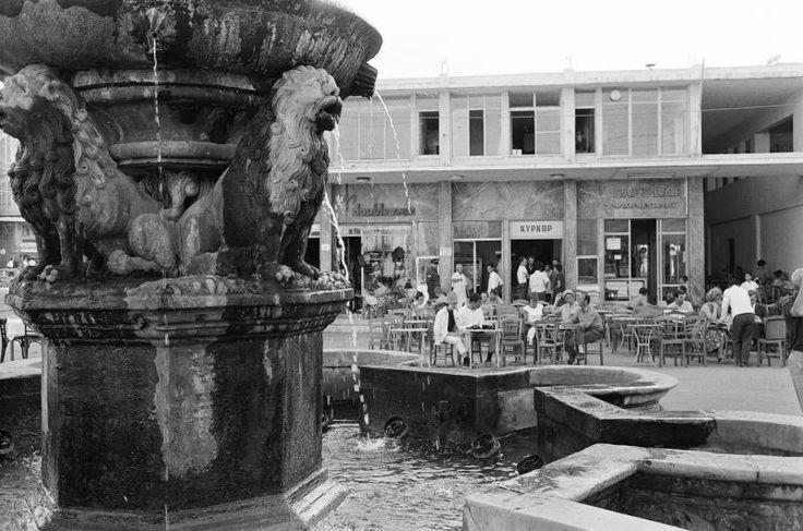 Η φωτογραφία τραβήχτηκε το 1962 από τον  Harry Weber ,και βλέπουμε να τρέχει νερό από τα στόματα των λιονταριών. Απέναντι το μπουγατζάδικο Κυρκόρ και μέσα στο στενό τα δυο σουβλατζίδικα.