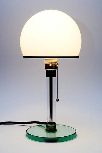The Wagenfeld lamp is today among the most famous lamps from the Bauhaus period. It has been designed in 1924 by Wilhelm Wagenfeld (1900-1990).It was here that he created the design classic W24, also called Wagenfeld lamp or Bauhaus lamp. With his metal and glass designs Wagenfeld became one of the most important industrial designers of his time.The WG24 Wagenfeld lamp consists of an opal glass cupola. The base and the post consist of clear glass and the enclosures consist of nickel-plated…