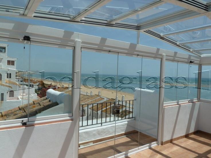 cerramiento de terraza compuesto por techo movil de cristal a dos aguas y cortinas de cristal