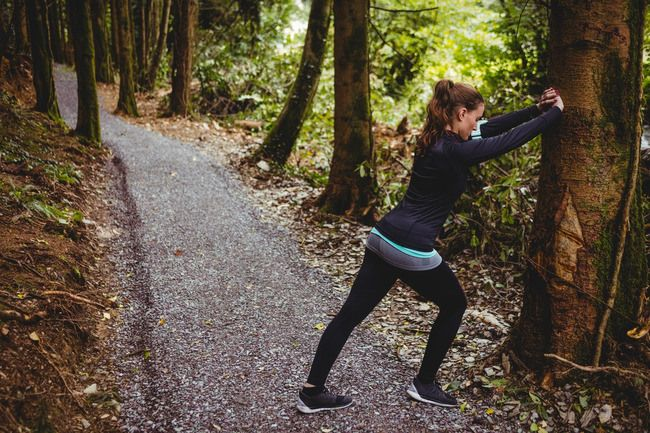 Fit brunette stretching against a tree in the woods