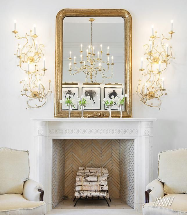Modern French living room features a white french fireplace accented with a herringbone firebox situated under a gold beaded mirror illuminated by stacked gold sconces.  Megan Winters House Beautiful: The Elegant Home | ZsaZsa Bellagio - Like No Other