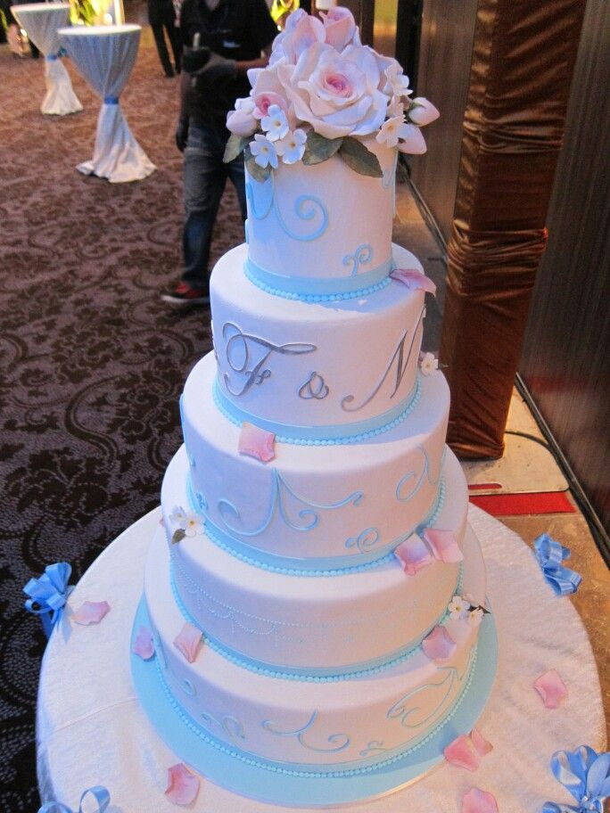 Simple wedding cake with cyan blue and white. Spirals and rose bouquet on top!