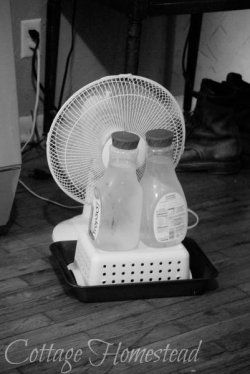 homemade air conditioner with a fan and 2 frozen bottles.
