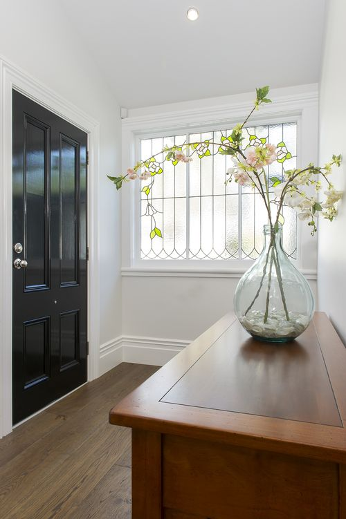 A front door in glossy Resene Black welcomes visitors. The walls are Resene Sea Fog. Photo by Mark Heaslip.