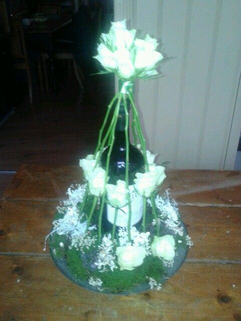 Een wijnfles met bloemen er omheen.