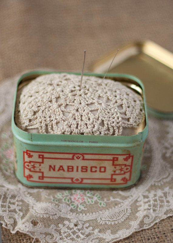 vintage box with a pincushion inside with a doily motif inside