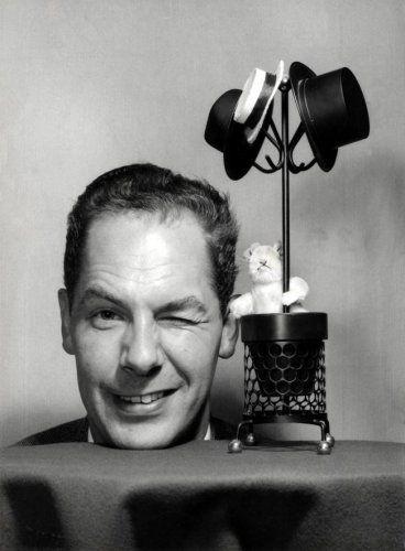 Theo Sanders | Opname van de beroemde goochelaar Fred Kaps (1926-1980). Zijn hoofd steekt boven een tafel met kleed uit en hij maakt een knipoog, op tafel staat vlak naast zijn hoofd een miniatuurkapstokje met drie hoeden eraan en een speelgoedkonijn in de mand ervan. Nederland, 1966.