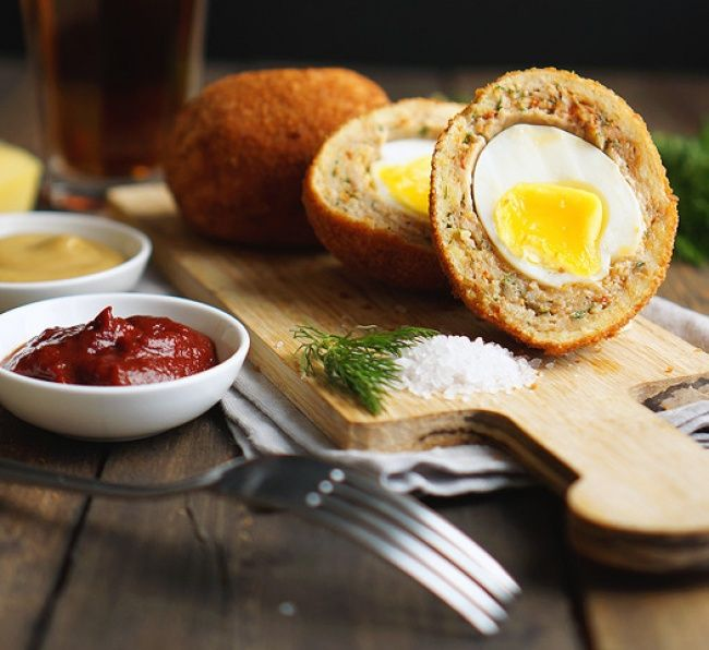 Scotch egg (шотландское яйцо) 3 яйца 250 г фарша 3 ст. л. муки зелень,соль, перец, специи — по вкусу Отварите яйца всмятку. Перемешайте в глубокой миске фарш, соль, перец, специи. Возьмите кусок фарша в руки, расплющите его на руке, как лепешку, обваляйте яйцо в муке и положите в центр лепешки из фарша. Залепите яйцо фаршем и скатайте в шар. Обваляйте получившиеся шары в муке и обжарьте до хрустящей корочки. Затем в духовку на 180гр.С/12 мин.