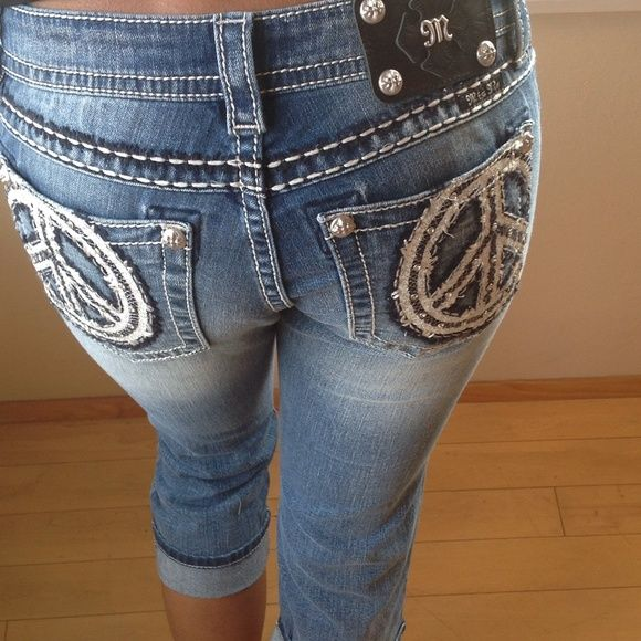 """Miss Me Capris ✄ᑭᖇIᑕE ᑕᑌT✄ Miss Me Capris ☮NWT Size: 28 MP7549P Faux Applique Peace Midrise Mid-rise medium wash capri with fading and whiskering. Back pockets feature a large embellished peace sign. Capri is detailed with crystal rivets and silver logo hardware throughout. PEACE ~pēs/ noun 1. freedom from disturbance; quiet and tranquility. """"you can while away an hour or two in peace and seclusion"""" synonyms:tranquility, calm, restfulness, peace and quiet, peacefulness, quiet, quietness…"""