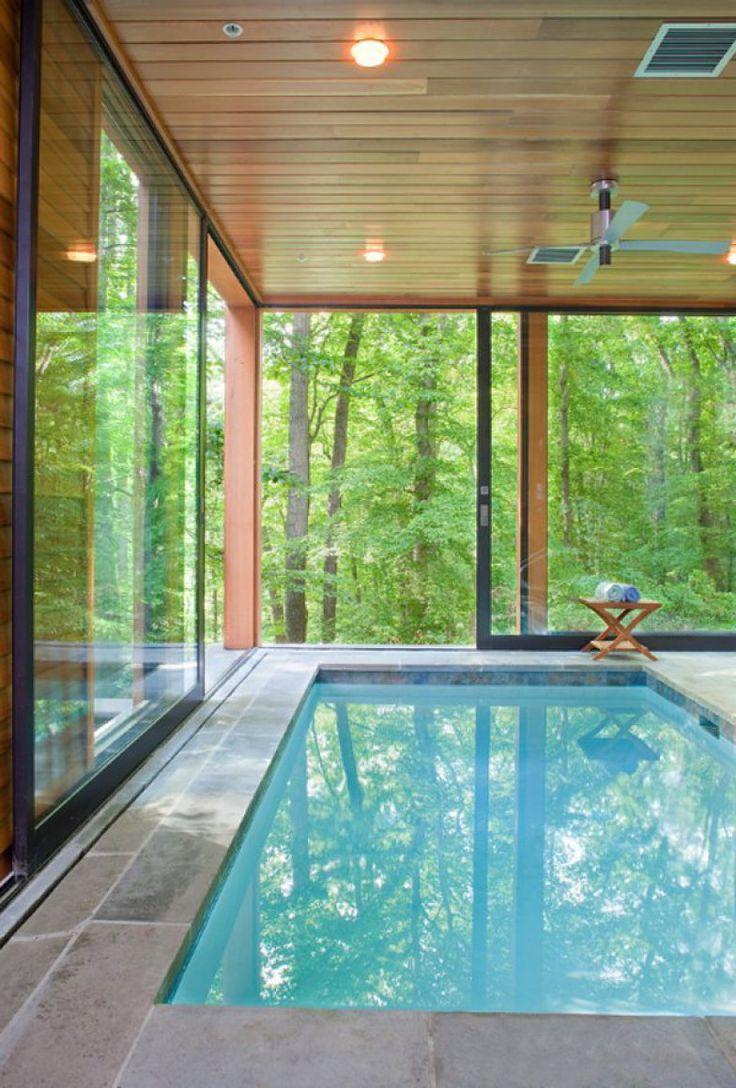 Minimalista, o ambiente escolheu a madeira e grandes painéis de vidro para valorizar a vista exuberante