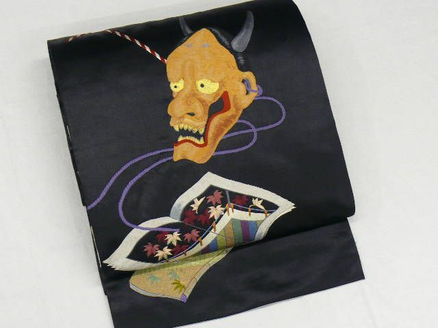 """Shusu Taikogara-Fukuro-obi"" with Hand-Embroidered ""Hannya"" Mask & ""Wabon (Japanese Old Book)"" Motif. ""Hannya"" originally means in Sanskrit ""wisdom to make a good life"". The ""Hannya"" mask of ""Noh"" Play stands for such one of women's faces as jealousy, anger and bitterness."