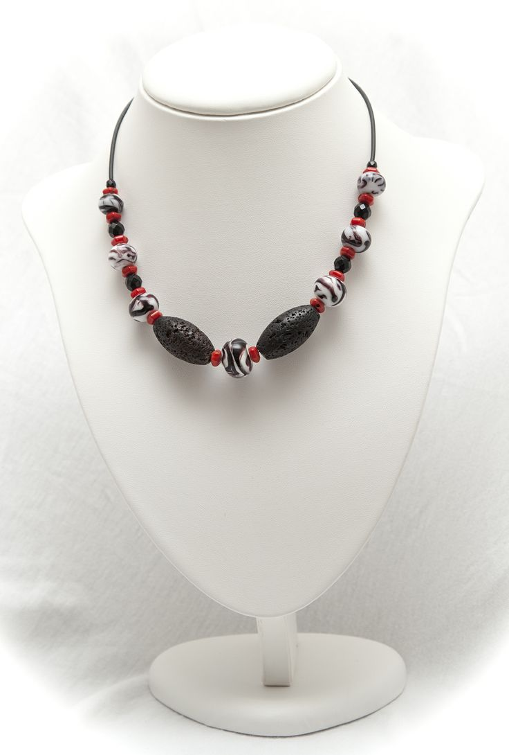 on a chain, a necklace of zebra stripe art glass beads and volcanic rock necklace, with onyx and coral beads