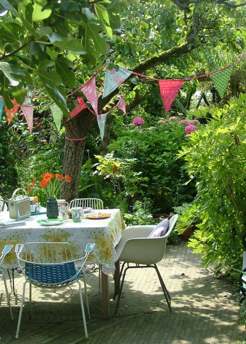 Bring the dinning room to the garden. Dinning room chairs, table cloth in the garden with festive bunting and vintage Roberts radio.