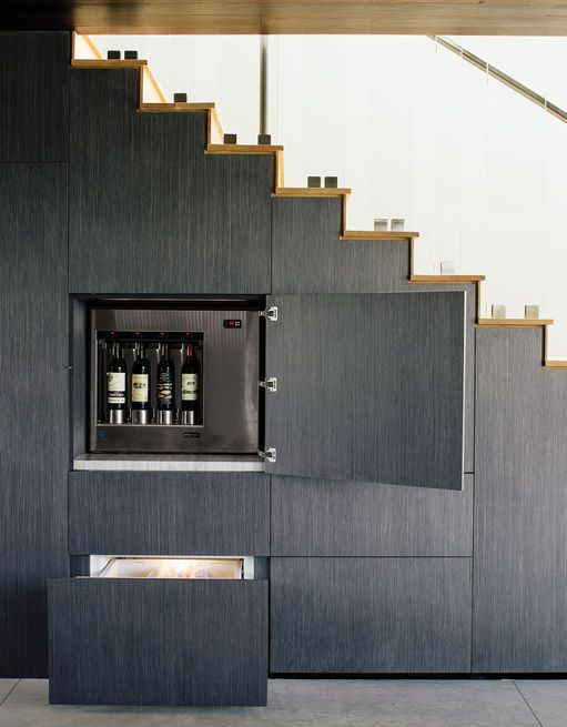 The wall beneath the stairs holds hidden storage, including an Enomatic wine dispenser and Sub-Zero refrigerated drawers. Photo by: José Mandojana