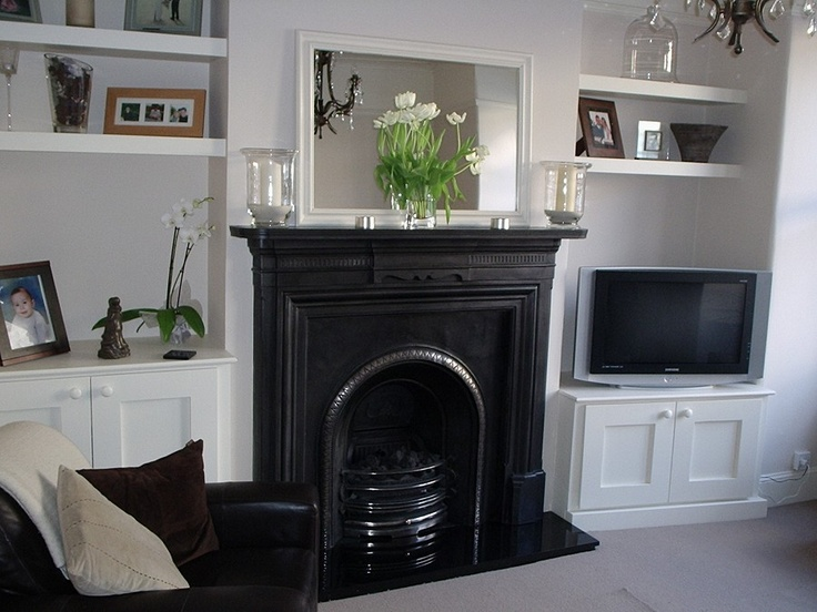 Shelves and cupboards built in by fireplace