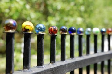 """Fort Worth, Texas garden wall built from salvaged materials - 1"""" glass marbles serve as finials on the salvaged iron fence"""
