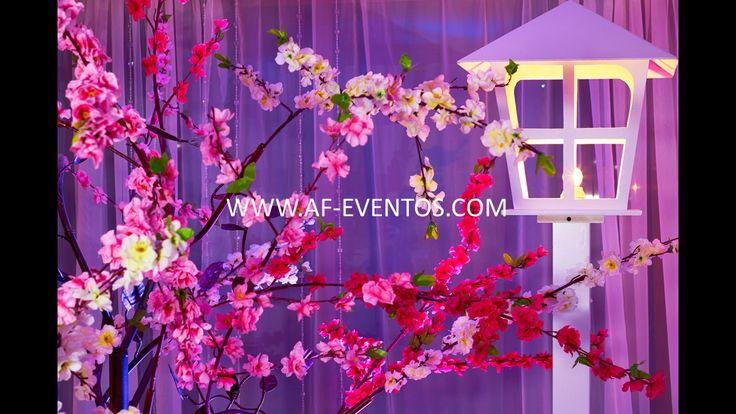 Entrada del salón, como stage de fotos, con faroles de luz cálida y árboles frondosos en tonos rosa, @afeventos