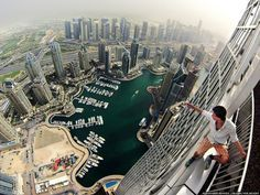 20 Images That Will Make Your Heart Stop © Alexander Remnev - Spectacular panorama of a city full of skyscrapers...Alexander holding on to the Cayan Tower in Dubai...