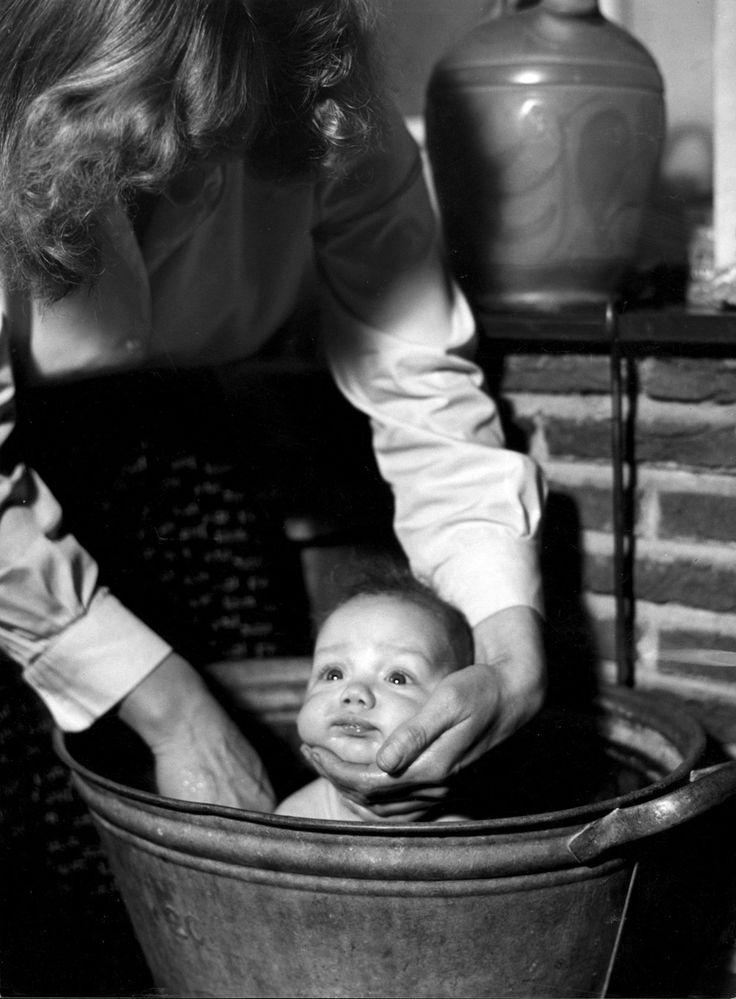 Moeder doet baby in een zinken teil in bad, met een hand onder het hoofdje van het kind 1957.