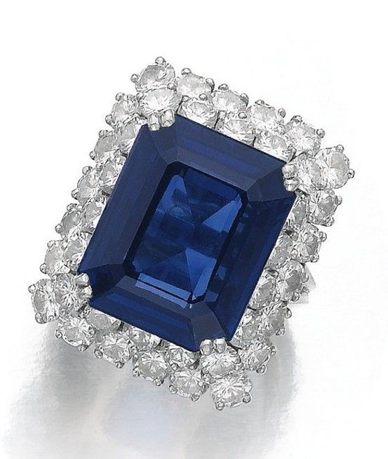 SAPPHIRE AND DIAMOND RING. The step-cut sapphire weighing 13.57 carats, within a double row border of brilliant-cut diamonds